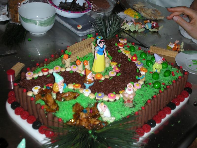 Fazendo um bolo de Branca de Neve. As flores e frutas são balas de goma. A grama é de coco ralado tingido com anilina verde. O caminho, de granulado.