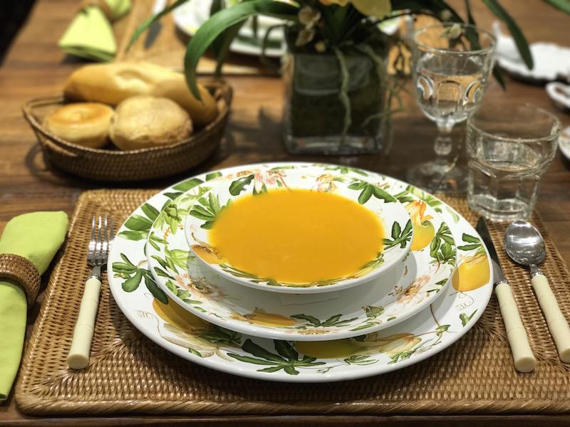 Sopa de abóbora sobre pratos da louça Passion Fruit, jogo americano de rattan, talheres com cabo plástico marfim e taças Goblet.