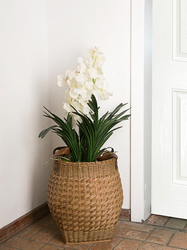A cesta do tipo balaio, com alças de couro, fica perfeita como cachepot. Seja de uma enorme orquídea como essa ou mesmo de uma pequena árvore em vaso. Mas atenção: em caso de plantas naturais, evolva primeiro o vaso e o pratinho em um saco de lixo antes de colocar na cesta, para evitar vazamentos. Cubra a parte de cima com pinhas ou lascas de madeira
