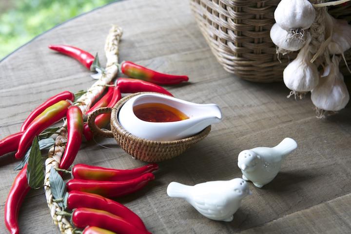 A pimenta é servida na molheira com base de rattan. Os passarinhos de louça são saleiro e pimenteiro.