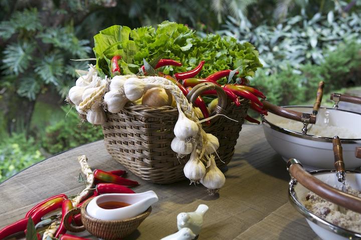 Couve, alho, pimenta e outros ingredientes trazidos da horta servem de decoração para a mesa, na cesta em rattan.