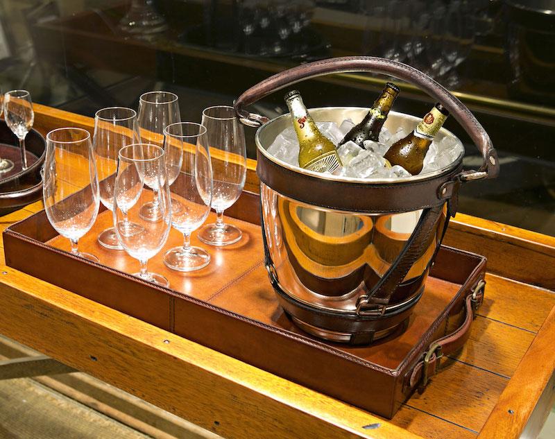 Bandejas de couro também ajuda a organizar o bar, delimitando a área de cada bebida: os copos de cerveja junto ao balde de gelo...
