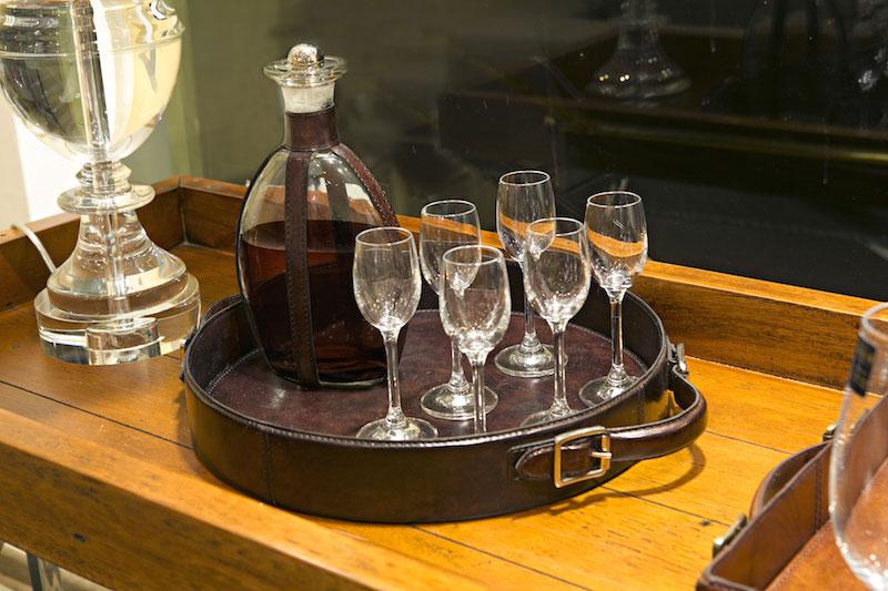 ...e os copos de licor na bandeja redonda, junto à licoreira com detalhes em couro.