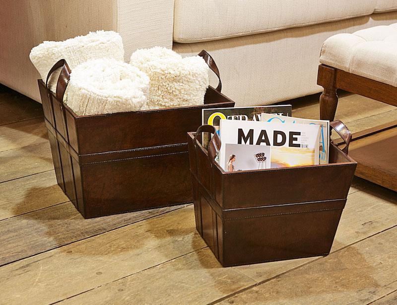 Na sala de estar, as caixas em couro, com alças, ajudam a organizar as mantas e revistas junto do sofá.