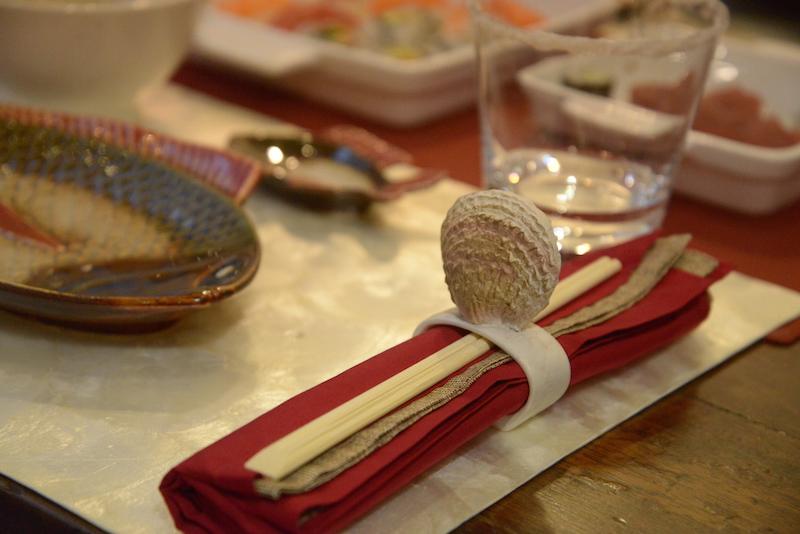 O guardanapo e os palitinhos ficam unidos pela argola de conchas, cada uma diferente da outra.