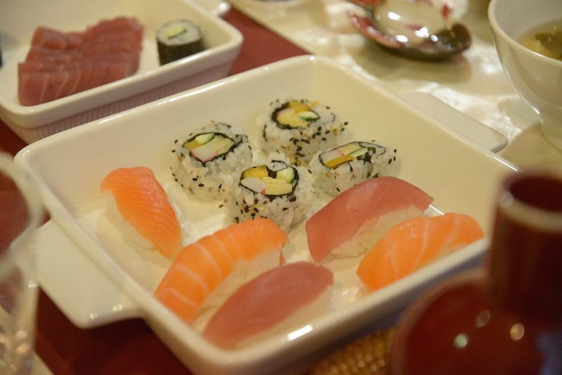 Sushi e sashimi são servidos nas travessas quadradas de louça branca.