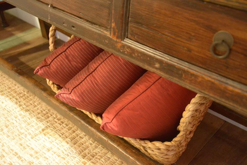 Uma cesta debaixo do aparador mantém almofadas extras à mão, para o conforto dos convidados.