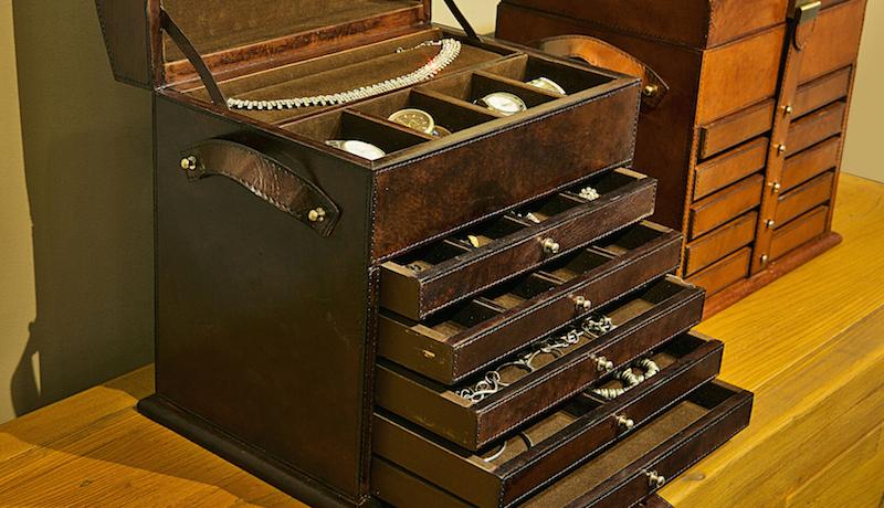 A caixa de joias mais alta tem cinco gavetas com divisões variadas, nichos para relógios e uma almofada para apoiar a joia mais usada. As alças de couro ajudam no transporte.