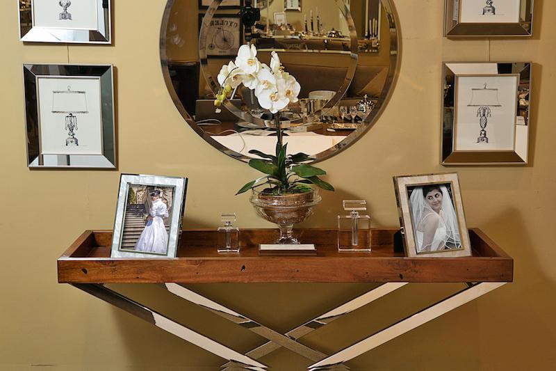 Aparador em aço inox, porta retratos, caixa em madrepérola, perfumeiras em cristas, espelho redondo e quadros Cecilia Dale