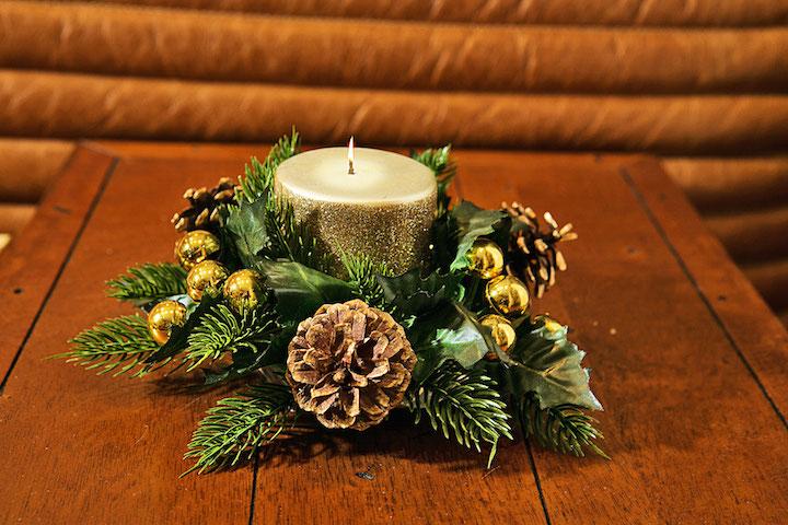 A vela dourada simples fica linda sobre uma mini guirlanda verde...