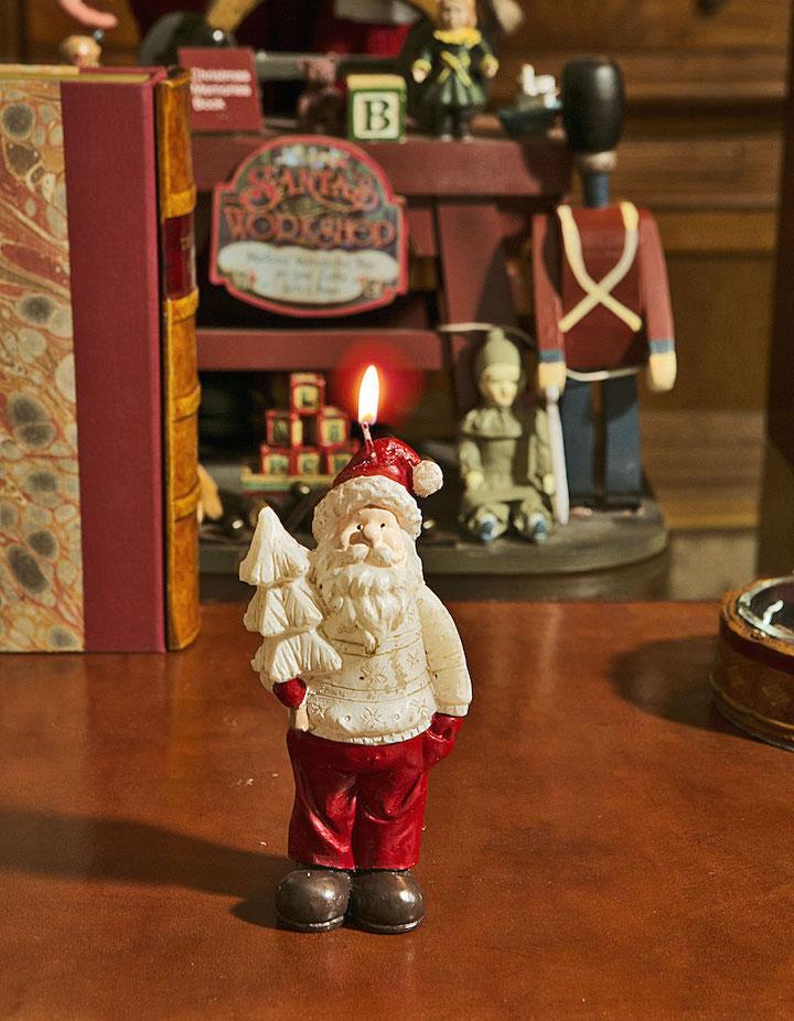Muito à vontade, o Papai Noel de suéter passeia entre os brinquedos.