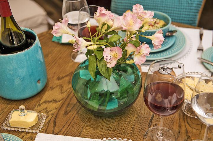 Não é porque você vai comer em casa que a mesa não precisa de capricho. Um bom vinho para acompanhar e flores no vaso de vidro azul fazem toda a diferença.