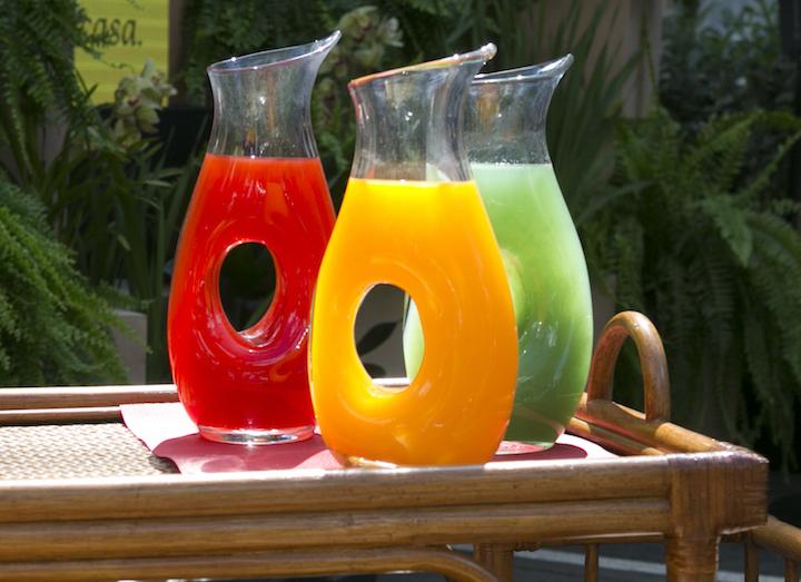 No carrinho de bebidas, jarras com sucos de frutas coloridos e um balde de gelo com champanhe. As ta©as, de cristla com titânio, mais resistente, são ideiais para um evento no jardim. E vem protegidas pelas cestas retangulares de rattan.