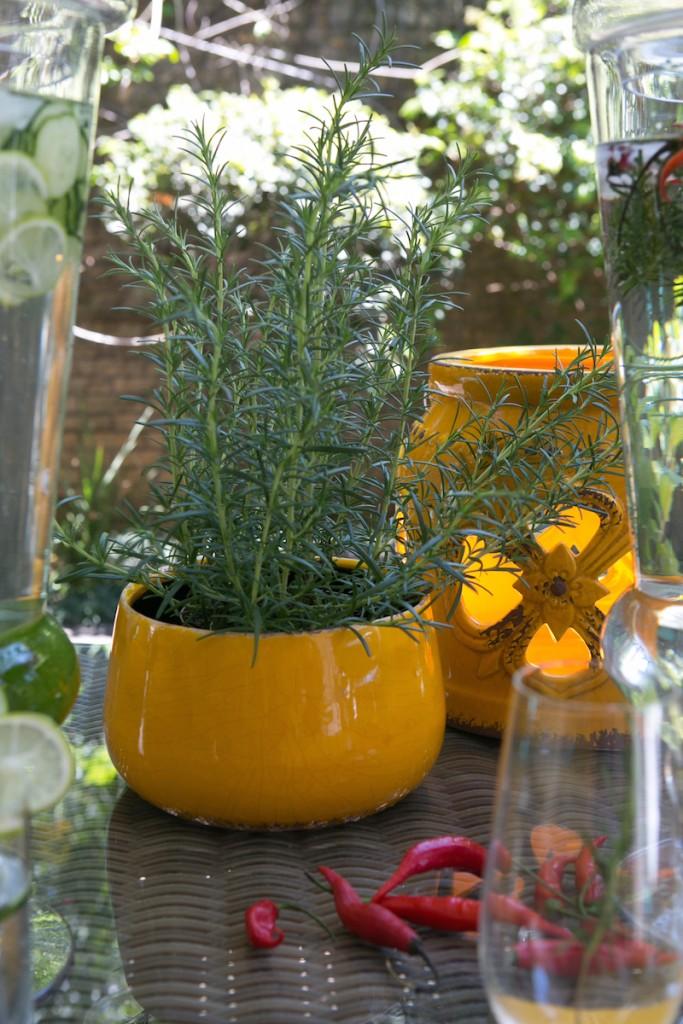 Os ramos de alecrum também enfeitam e perfumam a mesa, no cachepot xxxxx.