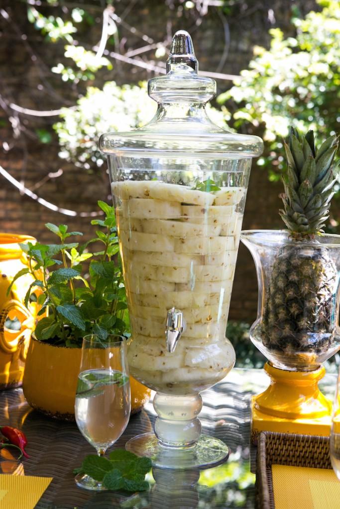 Enfeita a mesa com os próprios ingredientes da água aromatizada. O vaisnho de hortelã enfeita a mesa no cachepot amarelo e o abacaxi inteiro faz bonito no porta-velas La Fleche. Isso ajuda a identificar o que tem em cada suaqueira e ainda fica divertido.