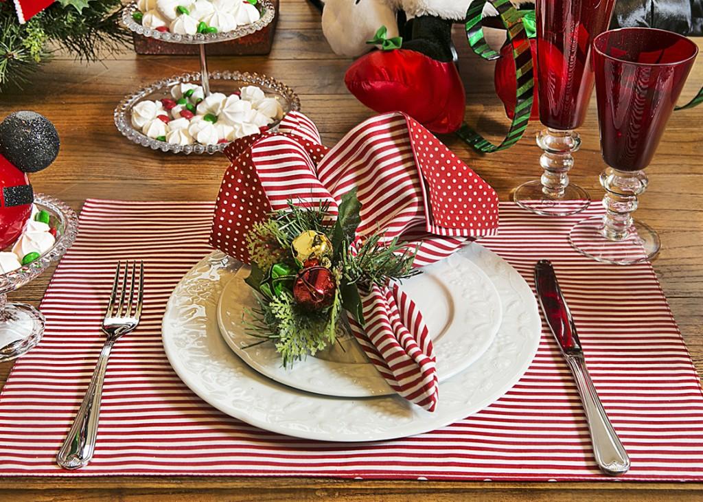 As bolinhas em vermelho e branco da roupa da Minnie aparecem no guardanapo e nos jogos americanos, entremeados por outros com listas. Cada guardanapo é preso por um enfeite de Natal da árvore.