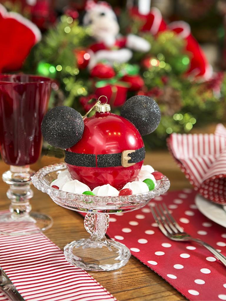 Em cada lugar, uma lembrancinha para cada convidado. E tem coisa mais fofa que essa bola com orelhas de Mickey, para cada um pendurar na sua árvore? O prato de vidro com pé Poas é recheado com mini suspiros e confeitos de chocolate só nas cores verde e vermelho, para combinar com a mesa.