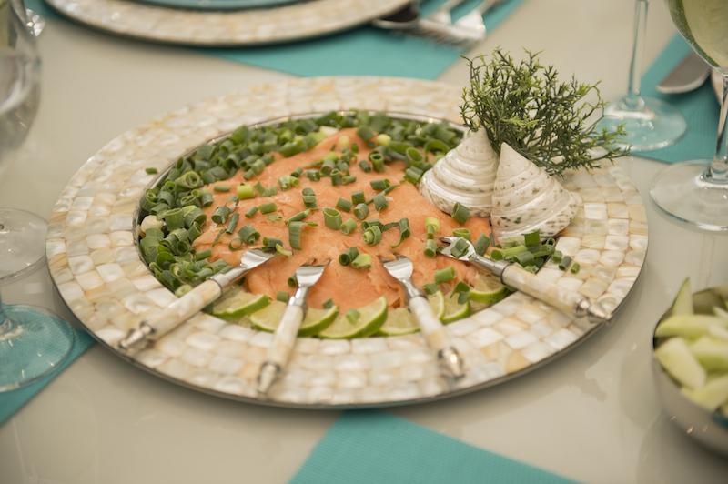 O sousplat de inox com borda de madrepérola serve de prato para o carpaccio de salmão. Enfeitado com fatias finas de limão, cebolinha e salsinha picadas, e regado com azeite. As conchas marinhas decoram o prato.