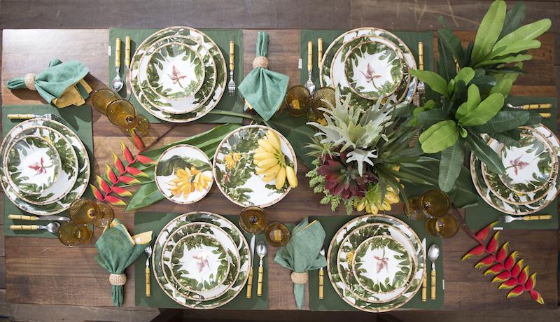 Sobre o tampo de madeira rústica da mesa de jantar James, usamos folhas e flores naturais de bananeira como base para o centro de mesa. Os pratos da cerâmica Bananas, cada um com uma pintura diferente, dão o resto do colorido bem tropical.