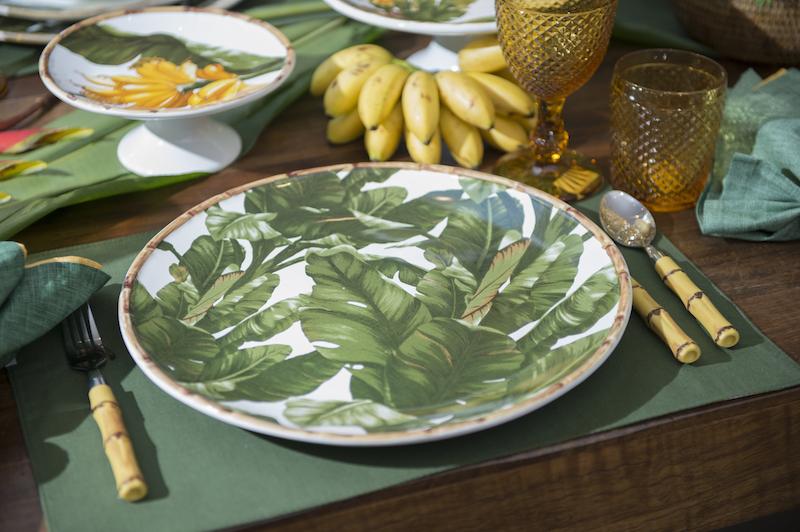 Um arranjo de suculentas no cahepot de rattan é arrematado por mais um cacho de bananas ouro. Cada prato da linha Banana tem uma pintura diferente. O prato raso tem um cacho de bananas entre as folhas. Já o sousplat em apenas folhas verdes com a moldura de bambu.