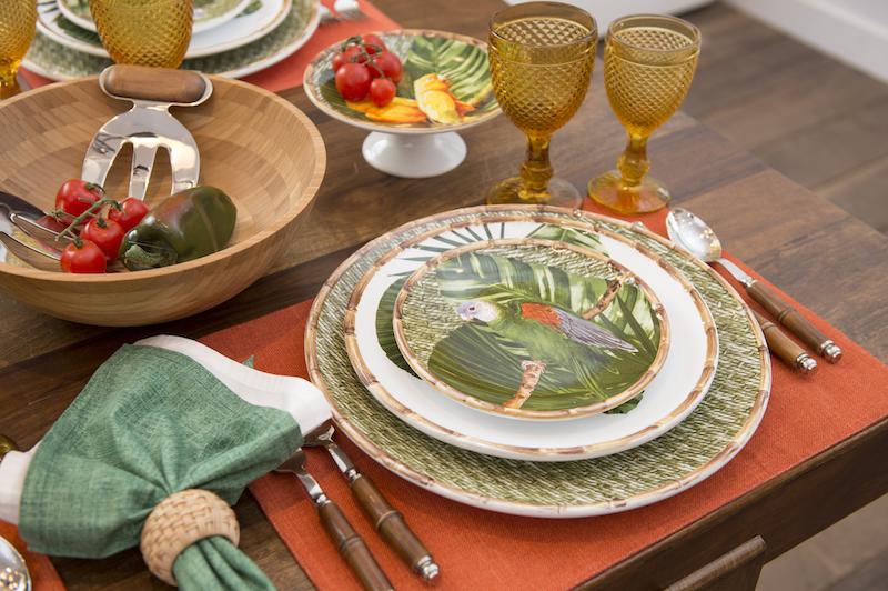 e o prato de maritaca verde. O prato raso tem apenas folhas sobre o fundo branco, e o sousplat, uma textura de palha trançada.