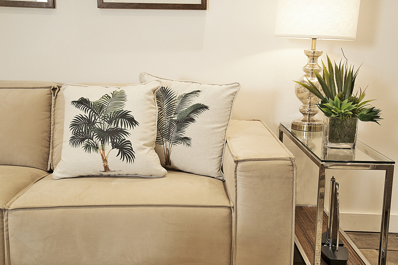 Duas variedades de coqueiro convivem pacificamente sobre o sofá Dogma, trazendo a brisa tropical para esse ambiente urbano e atual. Mesa lateral de vidro e aço,
