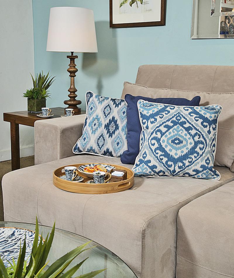O tom fendi do sofá Turim ganha um ar jovem e descolado com as almofadas azuis da linha Búzios. Sobre a bandeja redonda de bambu, as xícaras e pratos da linha quen inspirou as estampas. Abajur em madeira torneada xxx.