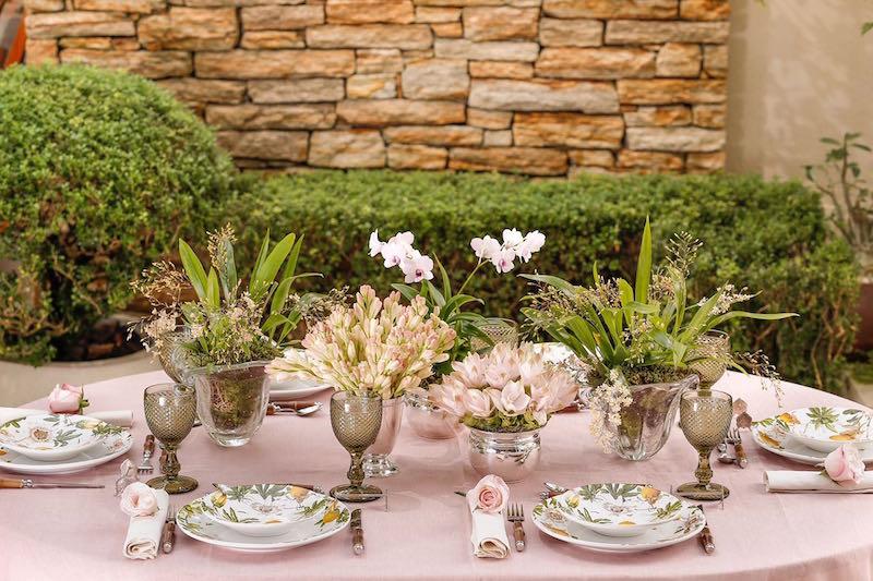 Para manter o clima romântico, Thais optou em puxar os tons de rosa suave da flor de maracujá para a toalha de mesa e os arranjos, deixando a louça em destaque.