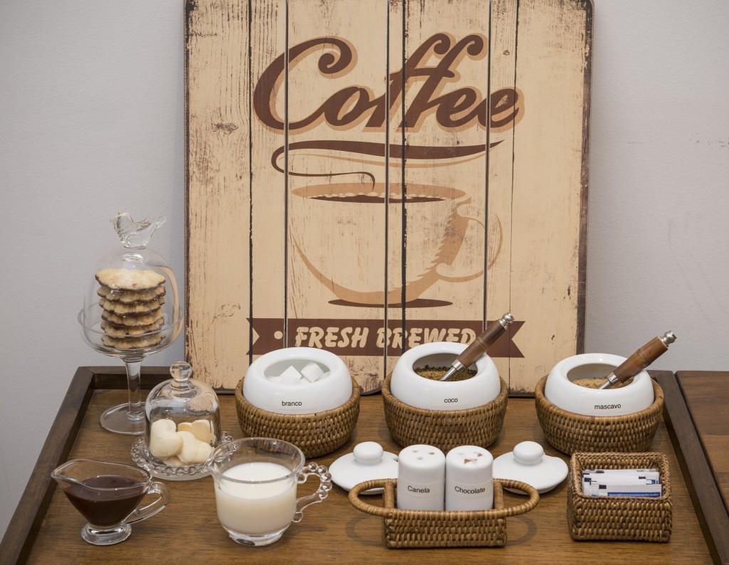 Coffee Bar montado com três tipos de açucar, cesta de adoçante, nutella, leite, biscoitos . Tudo pronto para receber os convidados.