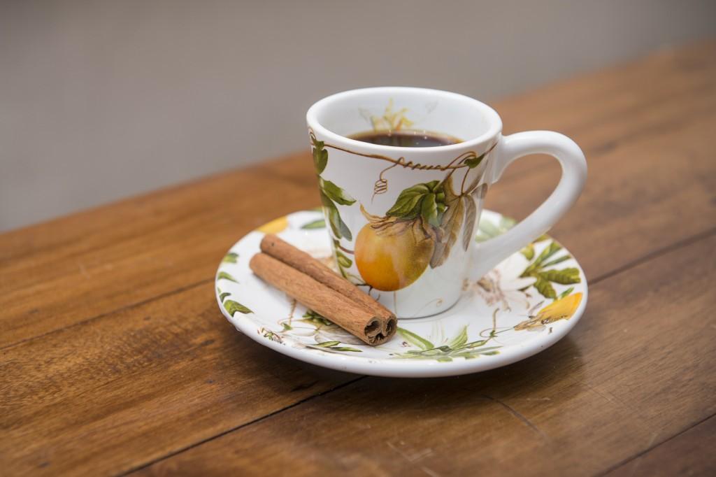 Xícara de café da linha Passion Fruit, acompanhada de um pau de canela como mexedor.