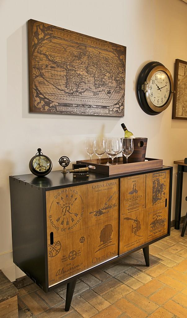 Degustar vinho em um ambiente bem decorado tem outro sabor. Aparador com róulos de caixas de vinho nas portas. O relógio XXXX traz um charme de velho mundo à bancada, ao lado do mini astrolábio e do pequeno telescópio em bronze.