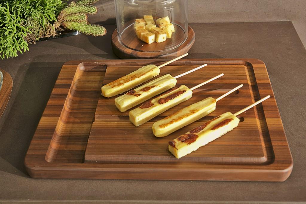 Pais churasqueiros vão gostar de uma bela tábua como a da linha Dark Teak, com frisos para escorrer a gordura. Atrás, porta queijos com tampa de vidro, da mesma linha.