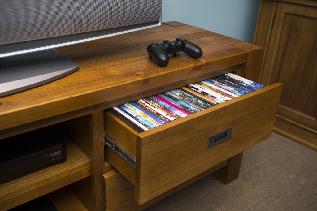 Gavetas no rack da sala de TV organizam os DVDs das crianças e os videogames.