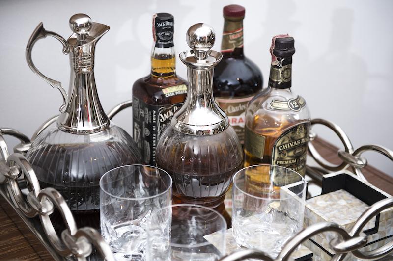 E as garrafas de vidro com alça niquelada guardam o bourbon e decoram.