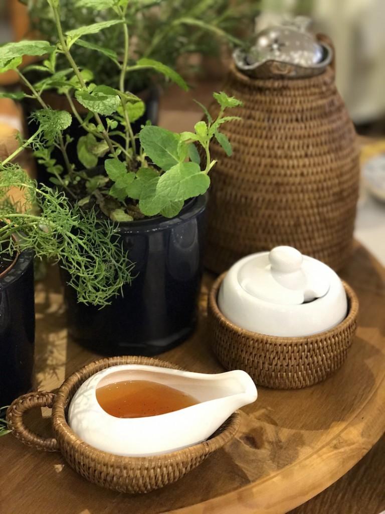 Para adoçar: mel, na molheira de rattan, e açúcar mascavo, no açucareiro. A térmica de rattan fornece água bem quente.