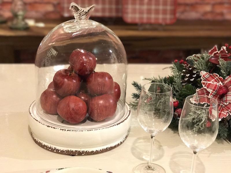 Prato com tampa de vidro recheado de maçãs vermelhas para centro de mesa.