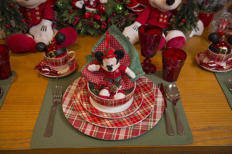 No lugar reservado para cada criança, várias surpresas os esperam. A primeira é o Mickey ou a Minnie sentados no bowl xadrez, servindo de porta-guardanapos. Copos vermelhos de vidro para o suco e o leite batido com chocolate. A louça xadrez Forest combina com as calças do Mickey, que veio muito elegante para festa de Natal.