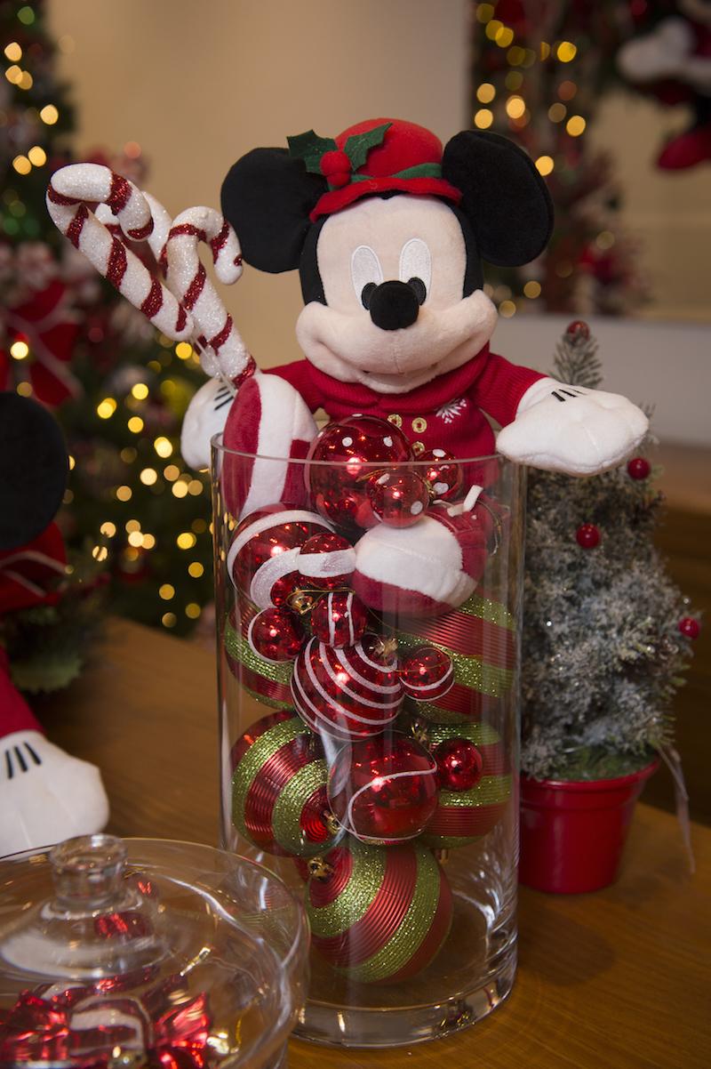 Enquanto as crianças comem, o Mickey guarda um cilindo de vidro cheio de bolas com orelhas, e segura um ramo com bengalinhas de Natal.