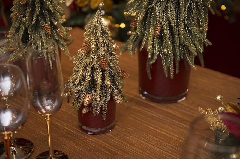 """Mini árvores cobertas de """"neve dourada"""" encaixam perfeitamente nos cachepots de vidro vermellho, preenchendo o centro da mesa."""