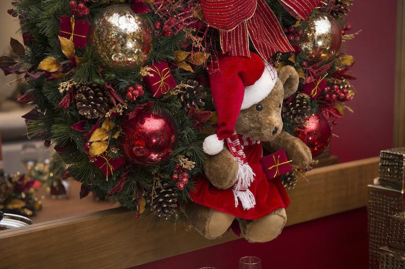 A guirlanda farta e exuberante traz a ursa de Mamãe Noel e muitos presentinhos entre bolas reluzentes.