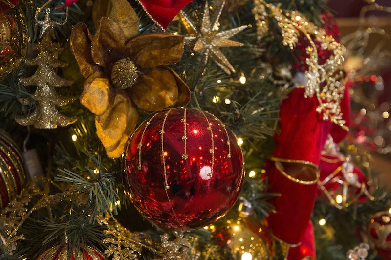 Magnolias e ramos dourados convivem em harmonia com as bolas vermelhas, criando uma fartura de reflexos,