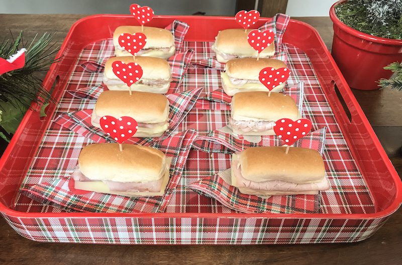 Com a ajuda da Mamãe Noel, a Minnie preparou com muito carinho sanduiches deliciosos para as crianças. Servidos em guardanapos de papel xadrez, na bandeja Forest.