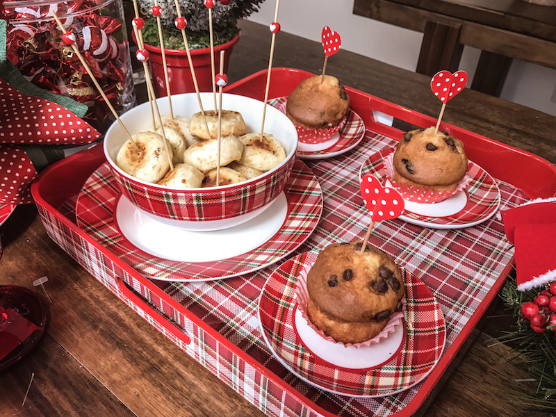 Na bandeja xadrez combinando com a louça, cupcakes vestidos de bolinhas e pão de queijo quentinho. Os palitos de coração dão clima festivo.......................................................