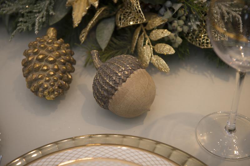 Pinha e avelã em madeira com patina dourada compõem a decoração da mesa da ceia de Natal.