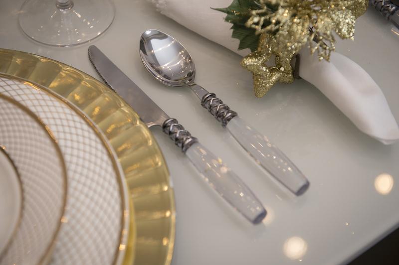 Os talheres homenageiam os cristais usados noa arranjos, com cabo de acrílico transparente. Um ramo natalino serve de porta-guardanapo.