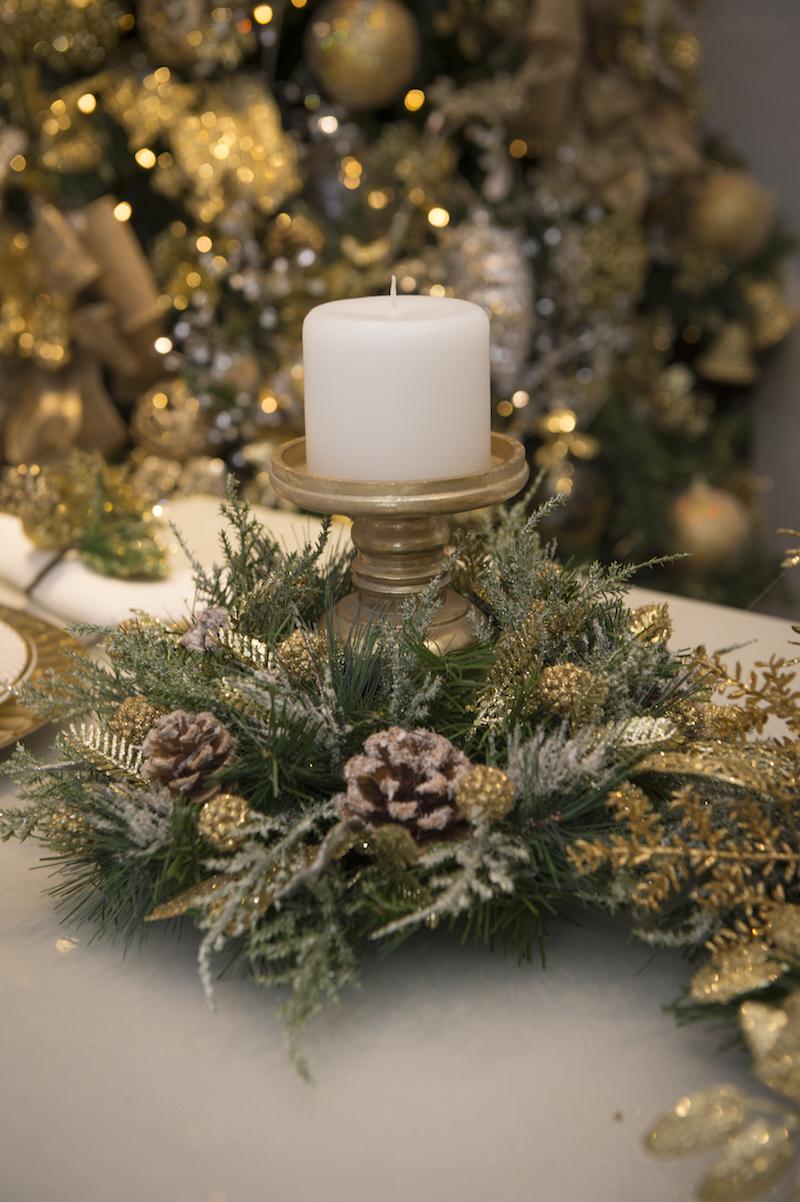 Os centros de mesa usam castiçais dourados rodeados por festoes verdes salpicados de pinhas e ramos.