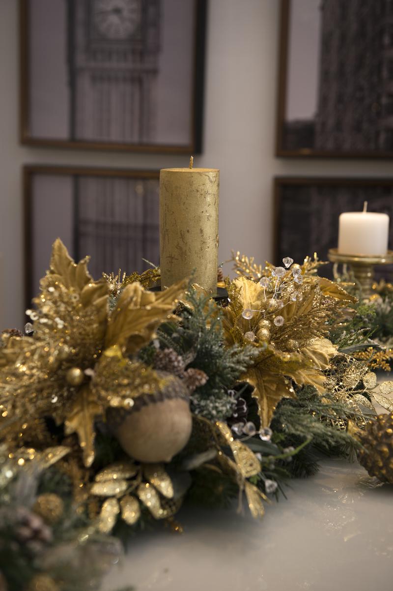 O centro de mesa une poisentias (a flor do Natal) douradas, misturadas a ramos de cristal, além de pinhas e nozes.