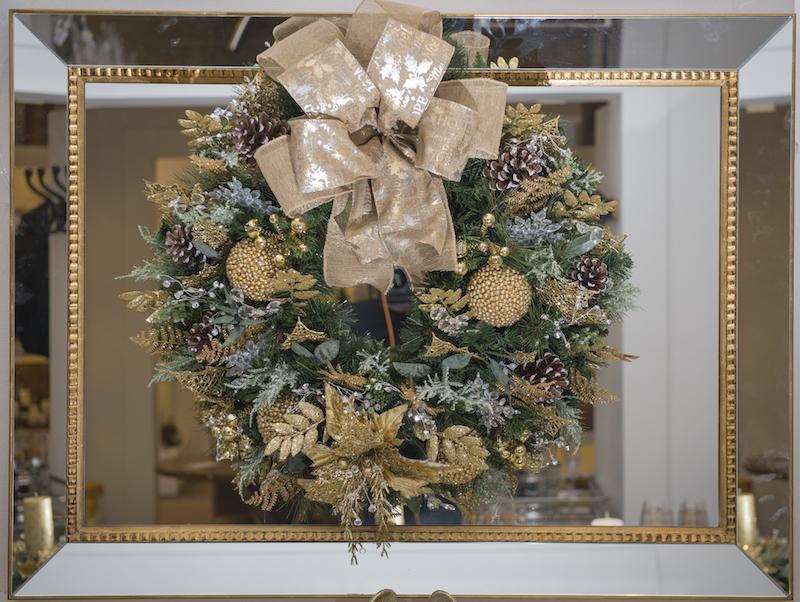 Sobre o aparador, o espelho com moldura dourada fica perfeito com a guirlanda, que tem laço com Feliz Natal escrito em várias línguas.