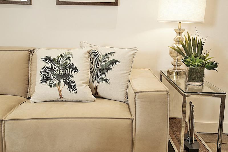 Almofadas de coqueiros, por exemplo, trazem o estilo Jungle para a sala sem precisar de muitos vasos.
