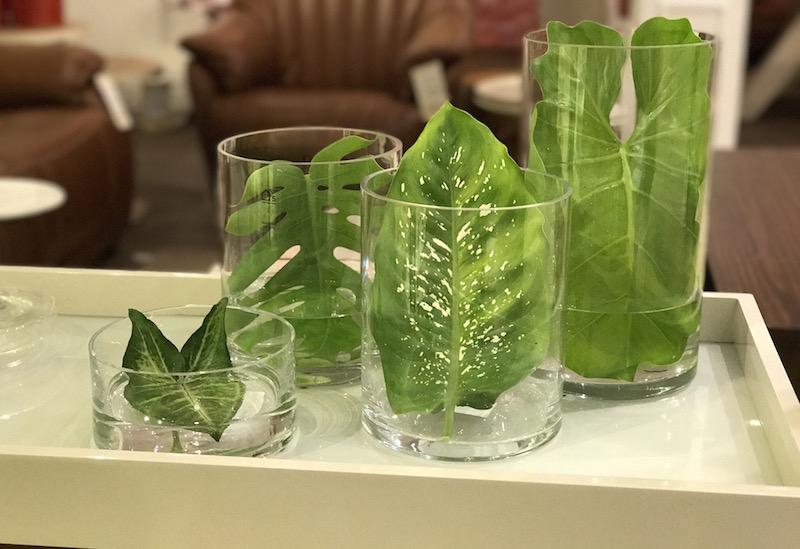 Folhas colhidas do jardim, em cilindros de vidro, formam arranjos mais efêmeros, mas que se encaixam perfeitamente na tendência. Solução rápida para dias de festa.